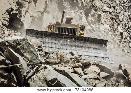 Bulldozer doing mountain road construction in Himalayas. Himachal Pradesh, India
