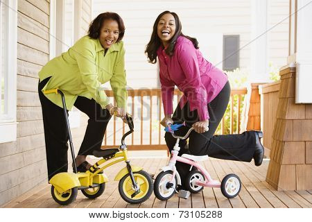 Mother and daughter riding tricycles on a porch