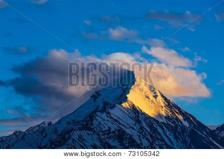 Snowcapped summit top of mountain in Himalayas in clouds on sunset. Himachal Pradesh, India