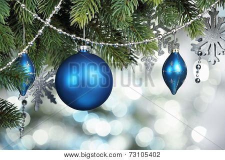 Blue Christmas balls hanging on fir tree