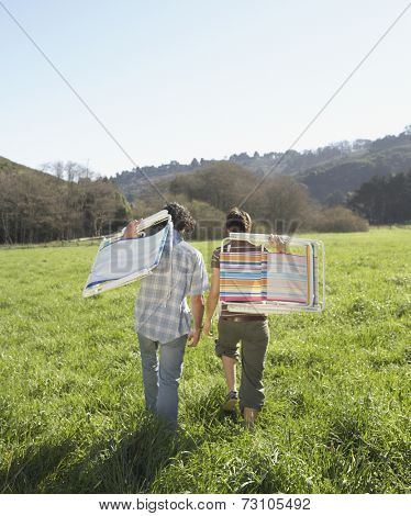 Couple carrying their lawn chairs across green meadow
