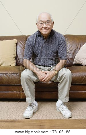 Portrait of elderly man sitting on couch