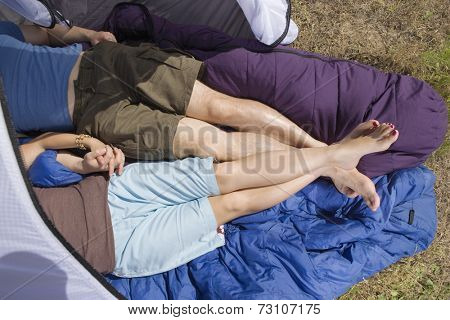 Lower body of couple laying in tent