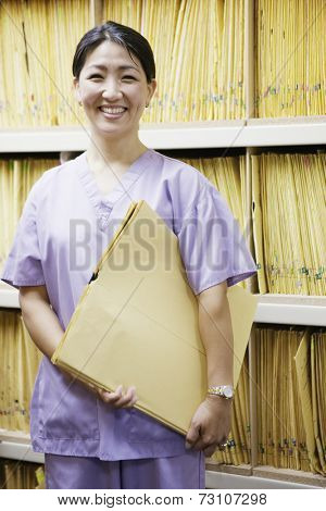 Portrait of female technician holding x-rays