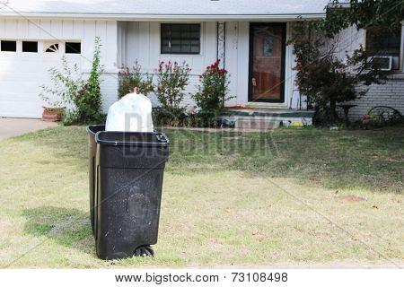 Large trashcan near a house