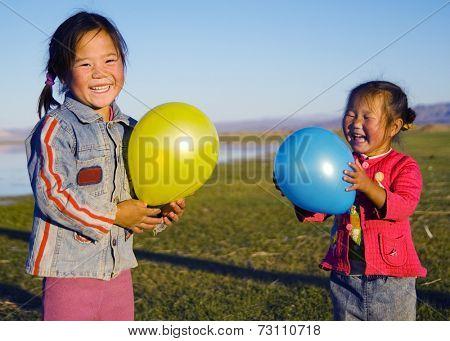 Asian girls playing by a lake.