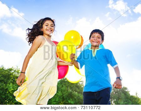 Little girl and a boy with balloons playing in the park.