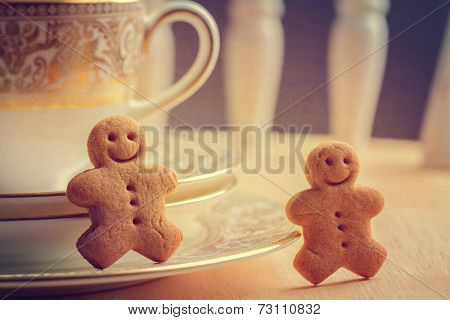 Happy gingerbread men sitting with antique teacups and saucers