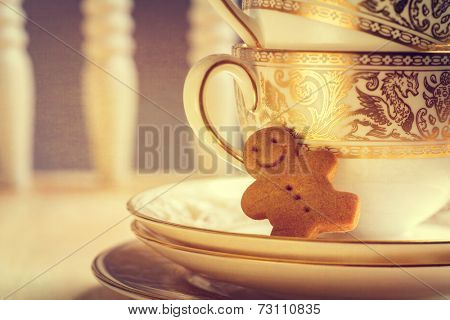 Happy gingerbread man sitting with antique teacups and saucers