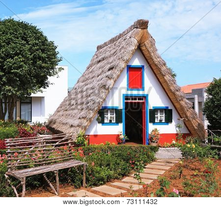 Traditional rural landscape. The little white house with a triangular thatched roof and a red door. The village - Museum of the Portuguese island of Madeira