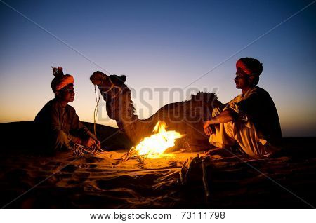 Two indigenous Indian men resting by the bon fire with their camel.