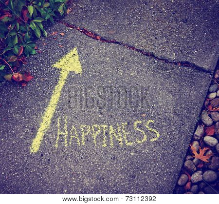 a yellow arrow showing the way to happiness written on a sidewalk with chalk toned with a retro vintage instagram filter effect (very shallow depth of field)