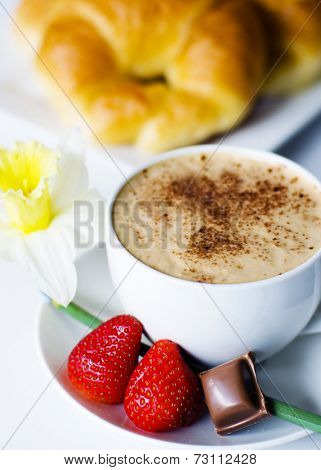 Decorated photo of cafe mocha, strawberries, chocolate, and croissant.