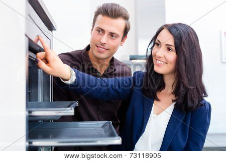 Woman picking oven for domestic kitchen in studio or furniture store showroom