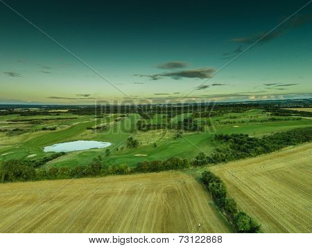 Aerial view of lush green farmland with ploughed fields and a lake or dam full of blue water in a scenic rural landscape