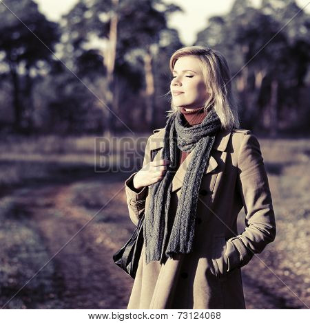 Happy young blond fashion woman in autumn forest