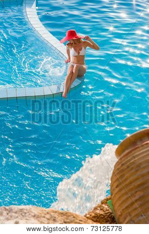 Woman with straw hat relaxing at the swimming pool