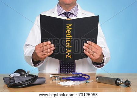 Doctor sat at a desk reading a Medical A-Z book