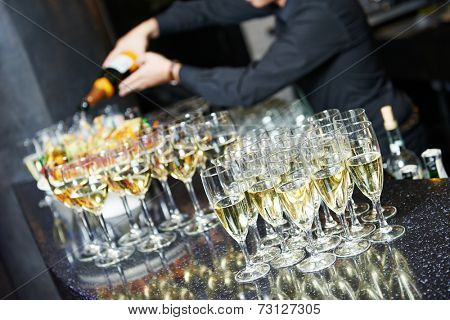 Waiter bartender pouring white wine into glasses at party event