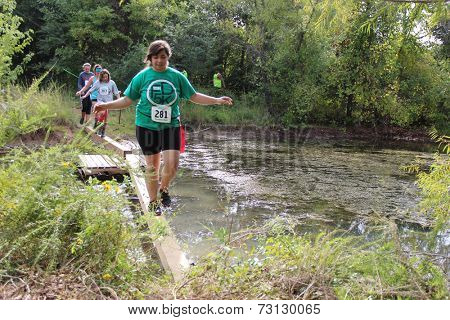 MUSKOGEE, OK - Sept. 13: Athletes run through zombie-infested forest and bog during the Castle Zombie Run at the Castle of Muskogee in Muskogee, OK on September 13, 2014.