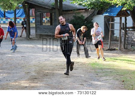 MUSKOGEE, OK - Sept. 13: Athletes overcome obstacles and rty to avoid bloody zombies during the Castle Zombie Run at the Castle of Muskogee in Muskogee, OK on September 13, 2014.