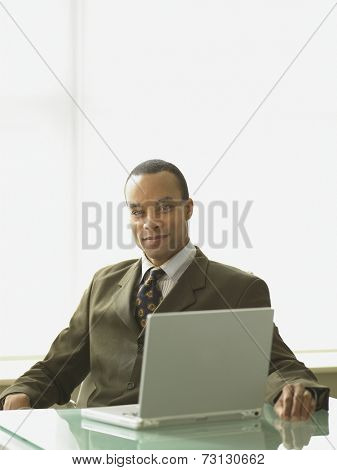 African businessman sitting at his desk with a laptop