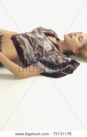 Studio shot of woman lying on floor with eyes closed