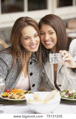 Two women taking a self-portrait at lunch