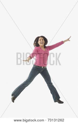 Portrait of mid adult woman jumping in air
