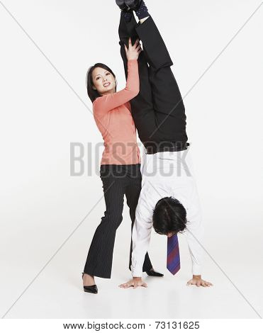 Studio shot of Asian businessman doing handstand with Asian businesswoman's help