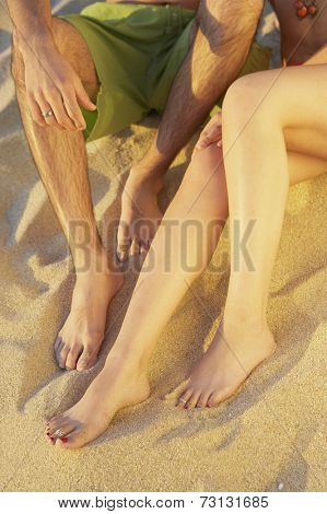 Close up of couple's legs on the beach