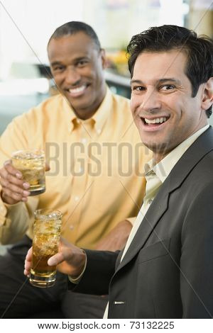 Two men smiling with drinks