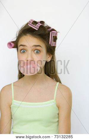 Studio shot of young girl with curlers blowing bubble gum