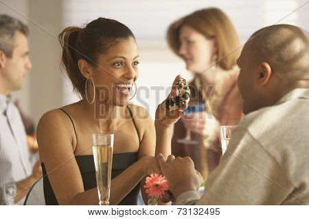 African man proposing to African woman at a restaurant