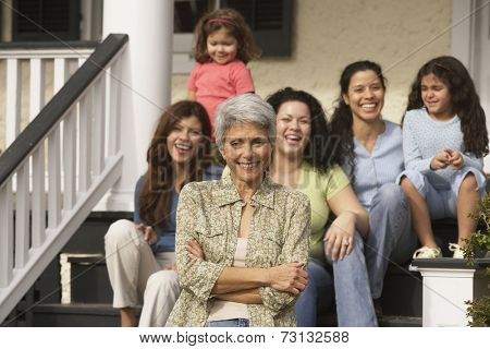Hispanic grandmother with female family members in the background