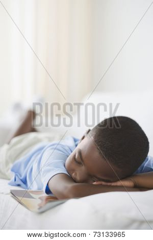 Young African boy sleeping with book on sofa