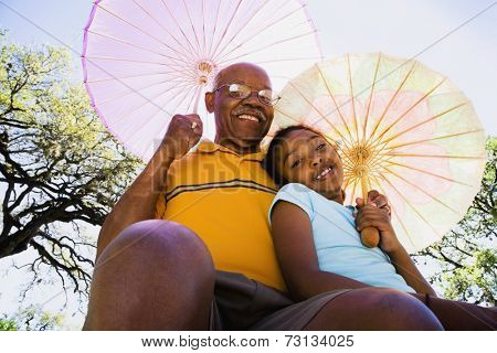 African American grandfather and granddaughter with parasols