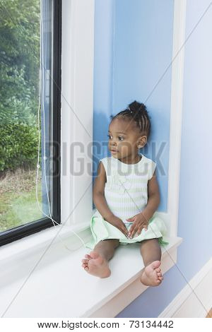 Young African girl sitting in window seat