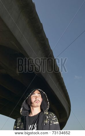 Young Asian man standing under raised highway
