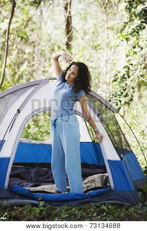 Woman stretching next to tent
