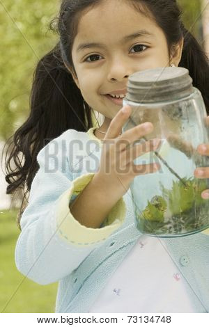 Young girl showing captured bug