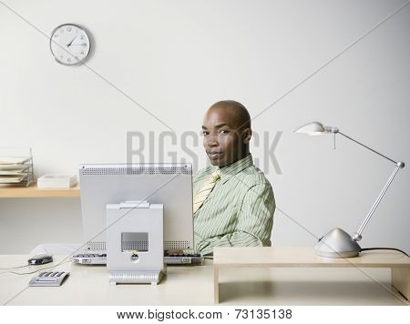 African businessman sitting at desk smiling