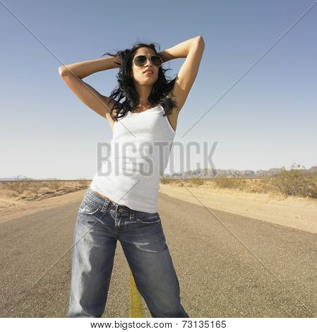 Woman standing in middle of deserted road with hands in hair