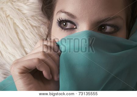 Close up of woman holding veil over lower half of face