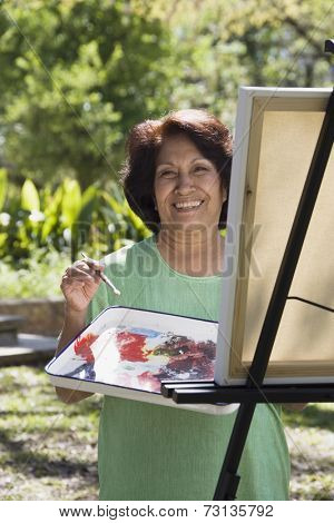 Senior Hispanic woman painting with easel outdoors