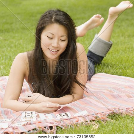Asian woman playing solitaire on blanket in grass