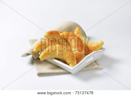 french buttery croissants, served on the wooden tray with fabric linen