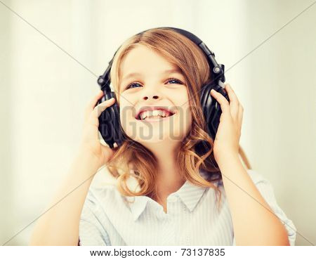 home, leisure, new technology and music concept - smiling little girl with headphones at home
