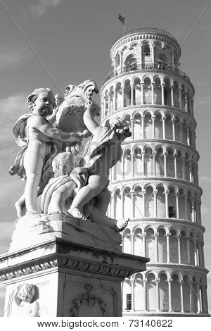 The Leaning Tower of Pisa and La Fontana dei Putti Statue, Italy. Black and white image
