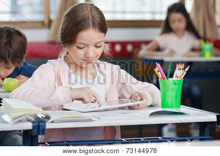 Little schoolgirl using digital tablet with classmates in background at classroom